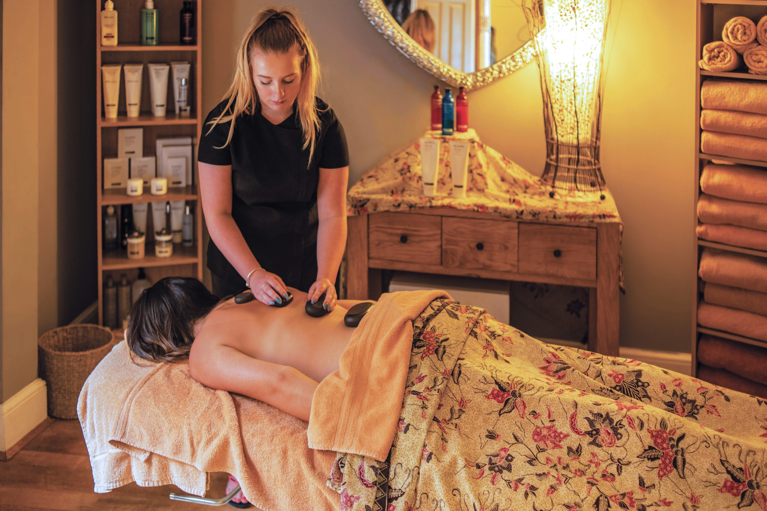 A female receiving a hot stone therapy treatment at the R&R Spa in Bideford North Devon